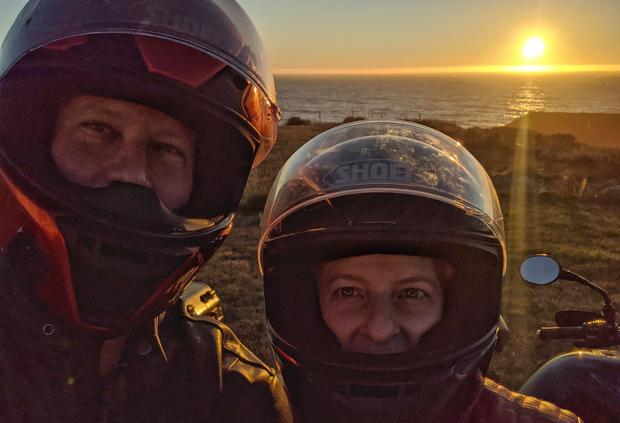 Seth and his wife wearing motorcycle helmets in front of a coastal sunset, northern California.